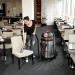 Extratora de carpetes CAR275 aspirando e extraindo líquidos de estofados sob limpeza